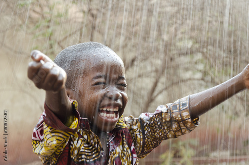 Fototapeta Little Native African Boy Standing Outdoors Under the Rain (Water for Africa Symbol)