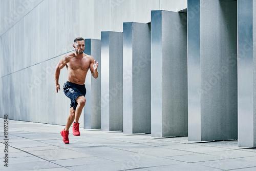 Handsome shirtless athlete jogging outside in modern urban setting