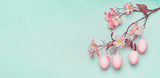 Easter border with hanging pastel pink Easter eggs and spring blossom at light at blue turquoise background.