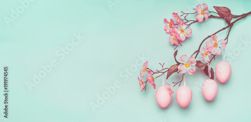 Plakat Easter border with hanging pastel pink Easter eggs and spring blossom at light at blue turquoise background