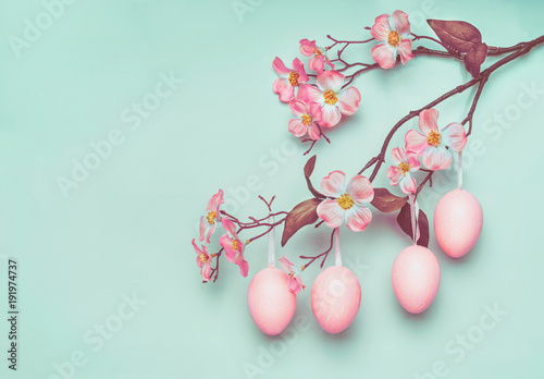 Plagát Pastel pink Easter eggs hanging on spring blossom branch at blue turquoise backg