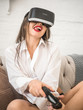 technology, augmented reality, entertainment and people concept - happy young woman with virtual headset or 3d glasses playing game at home