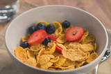 corn flakes with berries in white bowl for breakfast on table - 191981324