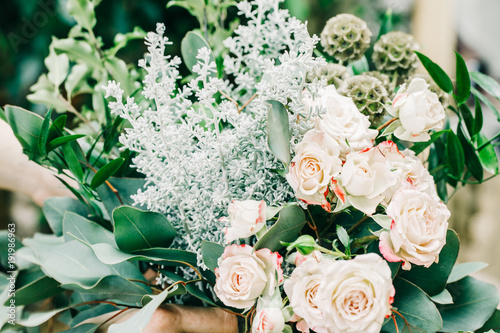 Wedding bouquet of white pink roses on flower shop background