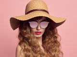 Gorgeous girl with Long and Shiny Curly Hair. Fashion Young woman in Hat and Sunglasses. Studio Portrait Glamour Beautiful Model with Trendy Stylish curly hairstyle. Summer Lady on Pink