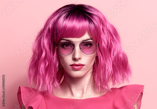 Fashion Portrait girl with Pink Hair, Trendy Sunglasses. Young woman in Stylish Outfit. Glamour Beautiful Model on Pink. Spring Summer Lady. Art Luxury fashion Style