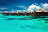 Over water bungalows with steps into lagoon with coral