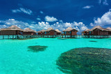 Over water bungalows with steps into coral lagoon