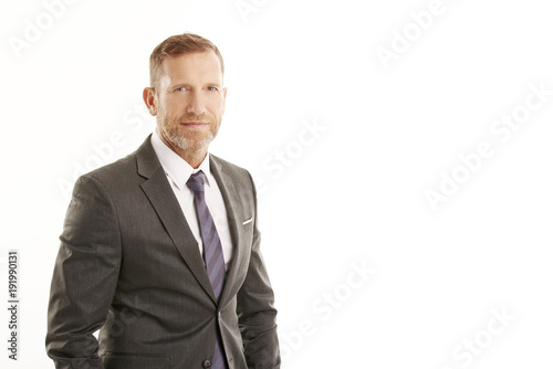 Smiling businessman portrait. Successful senior manager business man wearing suit while standing against at isolated white background.