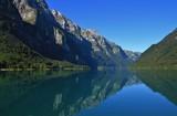 Glarnisch, mountain range in Glarus canton reflecting in lake Klontalersee. Quiet summer day in Switzerland.