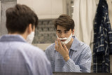 Portrait of teenage boy wearing pajamas shaving in morning, covering face with shaving foam and looking in mirror - 191995317