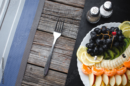 on a wooden background in a white plate fruit sliced, beautifully laid out