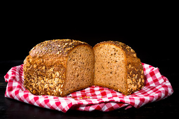 Granary spelt bread on red kitchen towel and black background