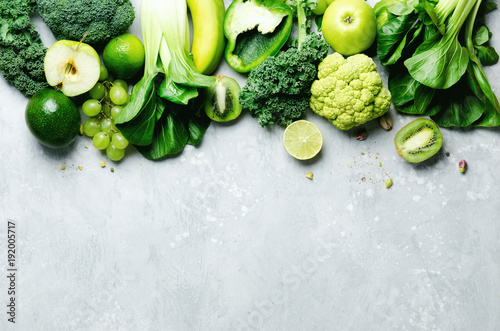 organic-green-vegetables-and-fruits-on-grey-background-copy-space-flat-lay-top-view-green-apple-lettuce-zucchini-cucumber-avocado-kale-lime-kiwi-grapes-banana-broccoli
