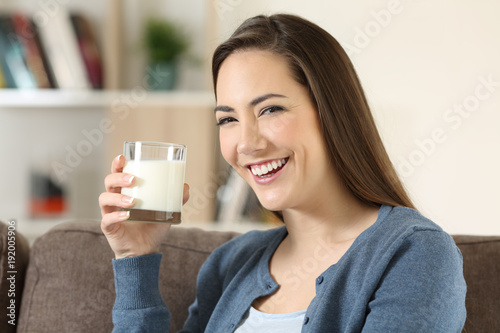 Fototapeta Woman holding a glass of milk looking at camera