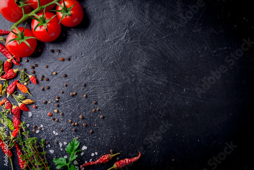 Fresh cherry tomatoes on a black background with spices with slate plate. Top view with copy space. - 192006747