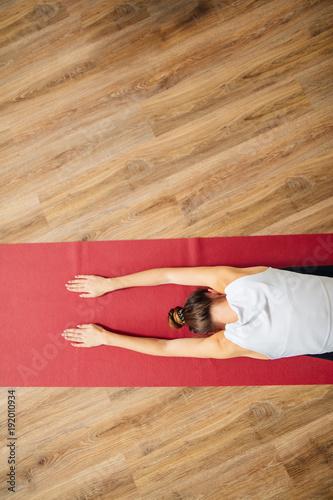 Woman doing the Child's pose on red yoga mat. Balasana