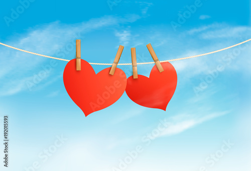 Two hearts hanging on a rope in front of a sky. Valentine's day vector.