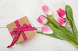 Women's day. Pink tulips and a gift on white background, top view