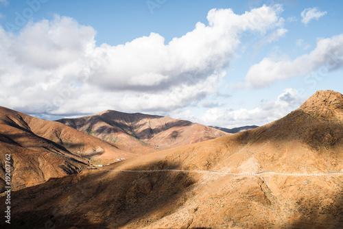 Aluminium Canarische Eilanden arid volcanic mountain landscape on Fuerteventura Island under partially clouded sky