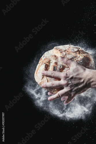 Closeup of male hands put fresh bread on black background with copy space for your text