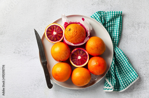 A group of oranges on a plate. some of them cut. knife and towel. on a stone background. a healthy summer table, the preparation of freshly squeezed juice or dessert