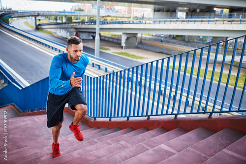 Handsome and athletic man jogging up a staircase during an outdoors workout