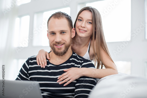 My beloved. Attractive glad long-haired young woman hugging her handsome boyfriend and smiling while he using a laptop