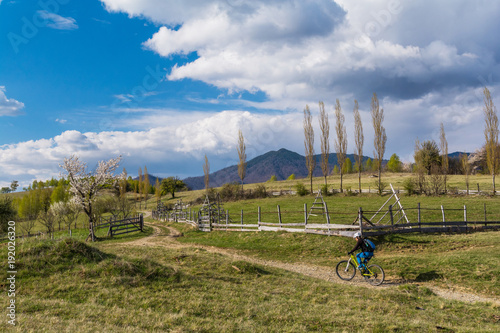 Woman cyclist in a beautiful spring landscape in the Carpathian Mountains, Transylvania, Romania with clouds and blue sky