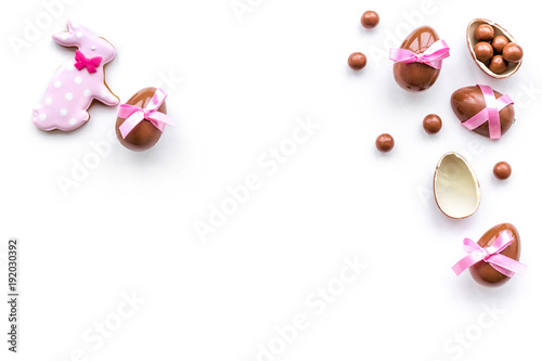 Celebrate Easter. Modern signs of Easter. Chocolate Easter eggs and Easter bunny cookies. White background top view copy space