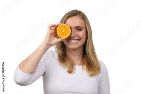 Hübsche blonde Frau hält eine Orange vor ihr Auge