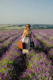 Cute girl with a flower wreath on her head and a suitcase in her hand in a lavender field - 192037775