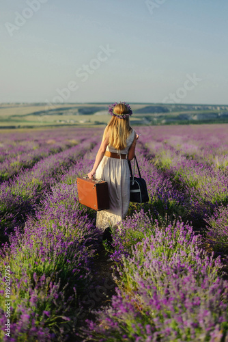 Cute girl with a flower wreath on her head and a suitcase in her hand in a lavender field