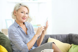Mature woman with hearing aid using smartphone indoors - 192039791