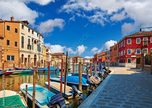 Burano island in Venice Italy over canal with boats among old