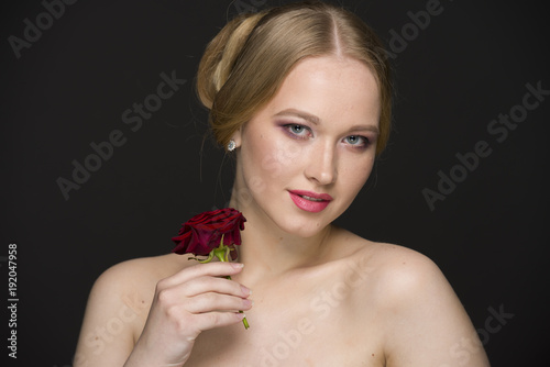 Papiers peints Salon de coiffure blonde with a red rose posing on a gray seamless background