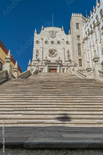 The stone front steps of the University of Guanajuato, with the front face of the building and a clear, deep blue sky, in Guanajuato, Mexico