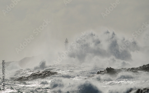 Aluminium Bleke violet Rough sea, big wave when breaking on the coast and silhouette of lighthouse in background, Telde, Canary islands