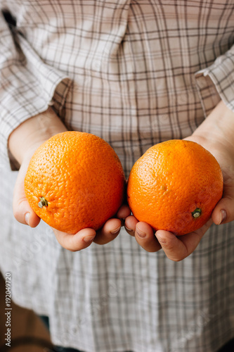 Woman holding two ripe oranges in her hands.