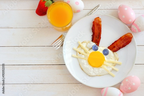 Easter breakfast with cute bunny face made of egg and bacon. Table scene, above view over a white wood background. - 192052353