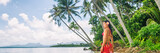 Tahiti luxury exotic travel vacation girl with polynesian flower walking on beach landscape with palm trees. Asian woman in red bikini and beachwear banner panorama. - 192060370
