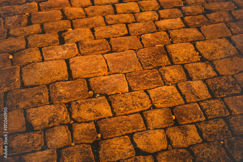 Fotobehang Stenen Night stone pavement pattern. Abstract structured background. Cobblestone street with golden light