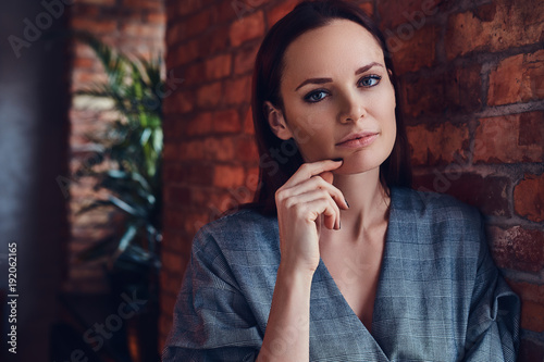 An attractive brunette woman in a room with loft interior.