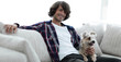 stylish guy sitting on the couch with his dog.