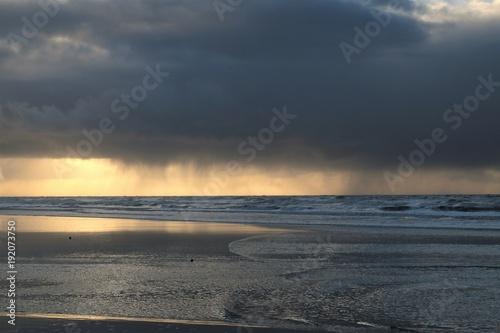 Papiers peints La Mer du Nord weiter Blick auf die Nordsee und das Wattenmeer mit dunklen bedrohlichen Regenwolken am Himmel