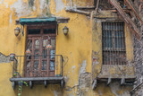 Old and decaying outer city wall, with a balcony with french wooden doors and iron railing, a double wooden window with iron bars, and yellow chipping paint, in Guanajuato, Mexico - 192074512