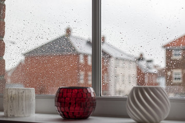 Rainy day depression. Selective focus on raindrops on modern house window glass pane. Time passing slowly.