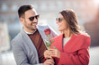 Man giving woman a rose.