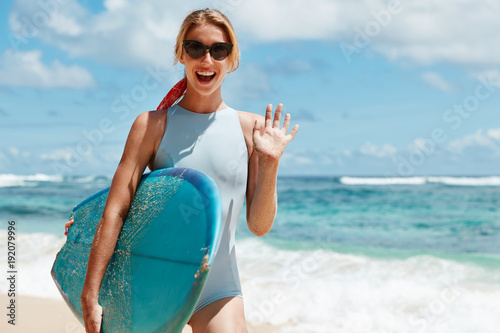Poster Pool Happy female in swimwear, waves with hand as greets with friend or participants of water sport competition, going to surf together, likes extreme activities, stands against ocean background.
