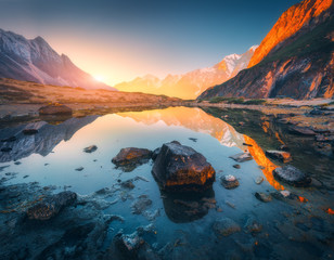 Beautiful landscape with high mountains with illuminated peaks, stones in mountain lake, reflection, blue sky and yellow sunlight in sunrise. Nepal. Amazing scene with Himalayan mountains. Himalayas © den-belitsky